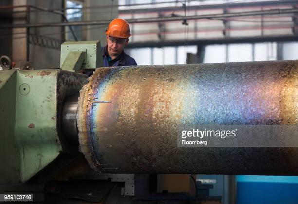 A worker machines the surface of an ingot of titanium alloy at the VSMPOAVISMA Corp plant in Verkhnyaya Salda Russia on Monday May 14 2018 The...