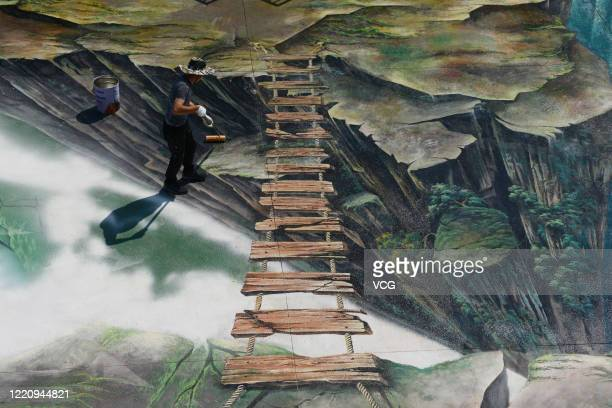 A worker maintains the 3D paintings on the ground at Longgang Scenic Area on April 24 2020 in Chongqing China