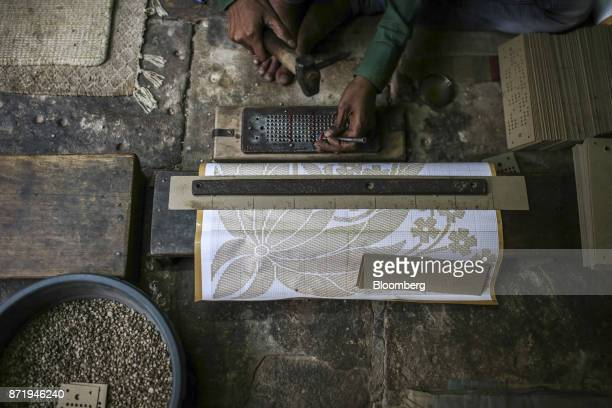 A worker makes a design template at a workshop in Varanasi Uttar Pradesh India on Saturday Oct 28 2017 In Varanasi where the manufacture of 45meter...