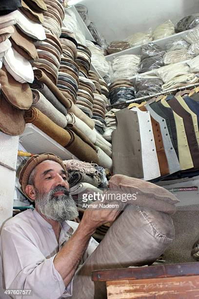 Worker makes a woollen cap called the Chitrali Topi in the North Western part of Pakistan. Typically worn by the pushtuns living in Pakistan and...