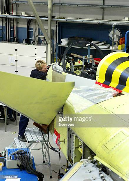 A worker makes an adjustment on a jet fighter under construction at the Saab Jas Gripen factory in Linkoeping Sweden Tuesday February 10 2004 Saab AB...