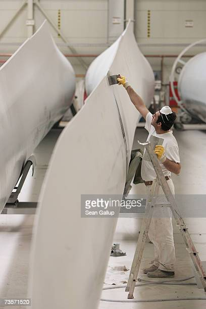 A worker makes final corrections on a 45 meter long wind turbine blade at the Nordex wind turbine factory March 12 2007 in Roctock Germany Nordex has...