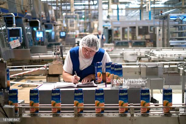 A worker makes notes as he monitors quality control for Tetra Pak cartons of Sandorabrand grapefruit juice as they move along the production line at...