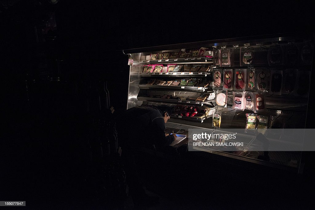 A worker makes notes at a refrigerator at Garden of Eden Gourmet which opened without power October 31, 2012 in Hoboken, New Jersey. Hurricane Sandy which made landfall along the New Jersey shore, has left parts of the state and the surrounding area flooded and without power. AFP PHOTO/Brendan SMIALOWSKI