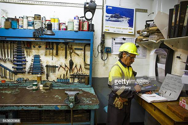 A worker makes notes in the equipment repair room on the Casablanca oil platform operated by Repsol SA in the Mediterranean Sea off the coast of...