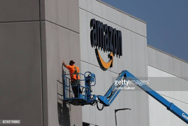 A worker makes repairs to a wall at a new Amazon fulfillment center on August 10 2017 in Sacramento California Amazon is preparing to open a new...