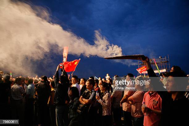 A worker makes smoke to heat up the atmosphere at the first 'Green Flag Erdos Grassland Rock Music Festival' near the Mausoleum of Genghis Khan on...