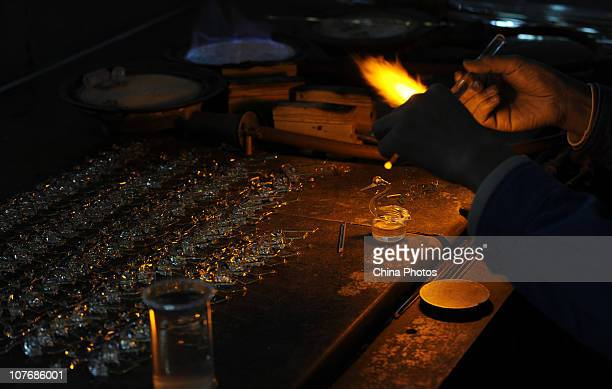 A worker makes the ornament of a spirit bottle with a blowpipe at a factory on December 17 2010 in Yibin of Sichuan Province China The factory...