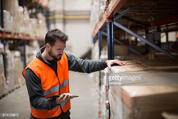 worker making a checklist in a warehouse with digital tablet - dock worker stock photos and pictures