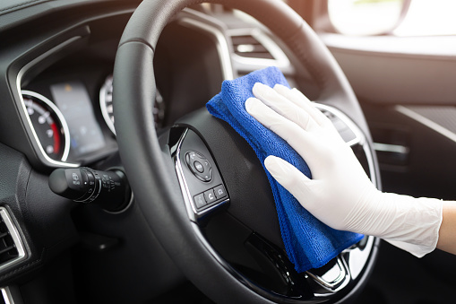 worker man wear gloves cleaning car interior console with microfiber cloth, detailing, car wash service concept. copy space. 1159012266