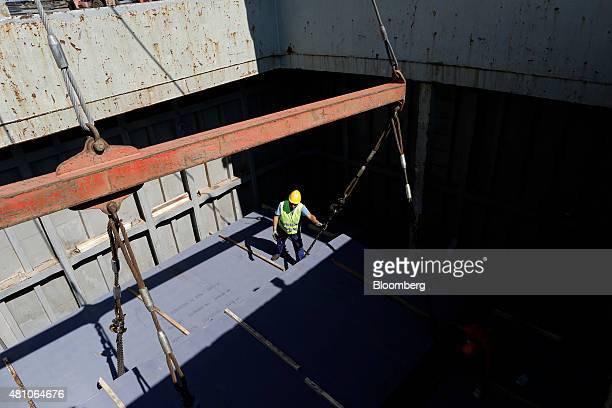 A worker maneuvers a winch as sheets of metal are lowered into the hold of a cargo ship at Thessaloniki port operated by Thessaloniki Port Authority...