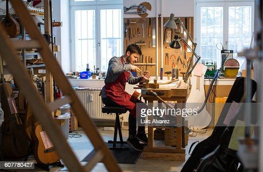 Worker manufacturing guitar at desk in workshop