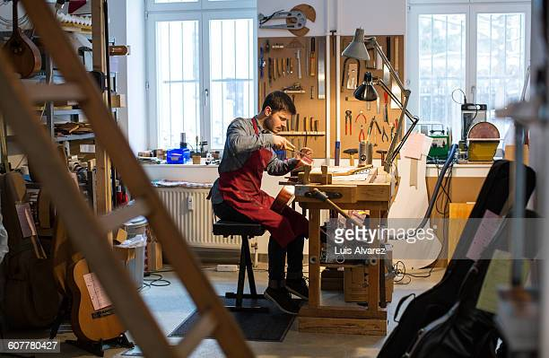 Worker manufacturing guitar at desk in workshop