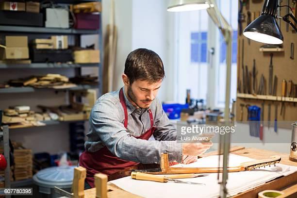 Worker manufacturing guitar at desk