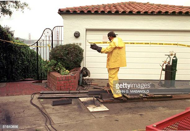 A worker measures a steel sheet of metal at a house that has been red tagged in San Francisco's Sea Cliff area overlooking the Golden Gate Bridge 14...