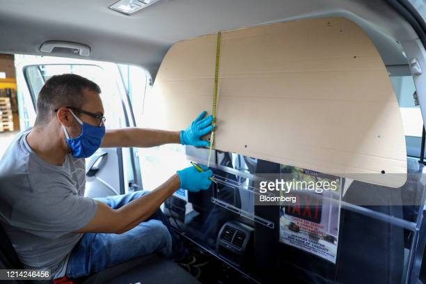 A worker measures a template as he installs a plexiglass barrier inside a taxi at Plexismart Srl in Guidonia close to Rome Italy on Wednesday May 20...