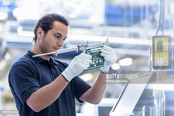 Worker measuring cut circuit board in circuit board factory