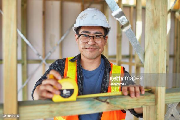 worker measuring frame with tape measure at site - building contractor stock pictures, royalty-free photos & images