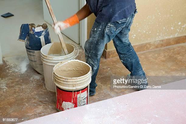 Worker mixing plaster in bucket