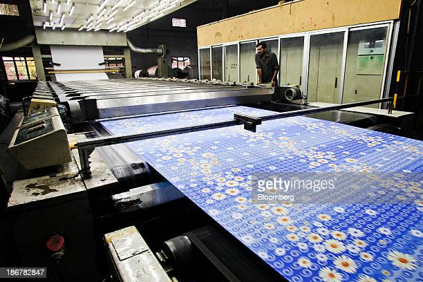 A worker monitors a roller printing machine at the Faisal Fabrics Ltd factory in Khurrianwala Punjab Pakistan on Saturday Oct 26 2013 Cotton imports...
