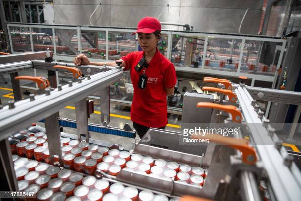 A worker monitors as cans of CocaCola Co brand Fanta carbonated soft drink move along a conveyor at the CocaCola Cambodia Bottling Plant operated by...