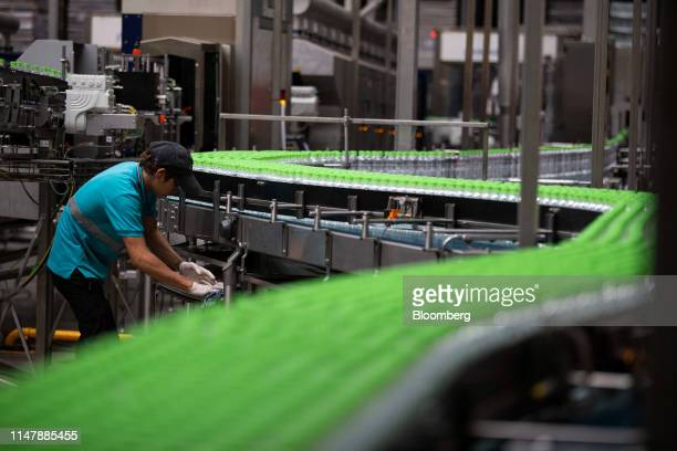 A worker monitors bottles of CocaCola Co brand water moving along a conveyor at the CocaCola Cambodia Bottling Plant operated by Cambodia Beverage Co...