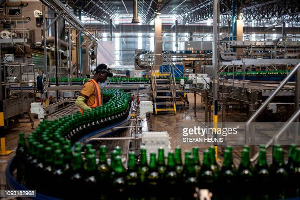 A worker monitors newly bottled beers on the production line at the InBev beer factory in Ogun State outside Lagos outside Lagos on November 7 2018...