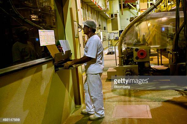 A worker monitors one of the machines used in making pasta at an Alicorp SAA food processing plant in Machado Brazil on Wednesday May 14 2014...