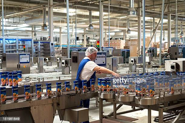 A worker monitors quality control for Tetra Pak cartons of Sandorabrand grapefruit juice as they move along the production line at PepsiCo Inc's...
