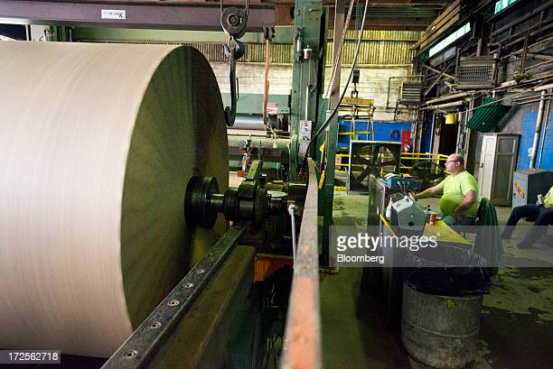 A worker monitors rolls of paper as they are loaded onto the paper mill at Newark Recycled Paperboard Solutions in Baltimore Ohio US on Tuesday July...
