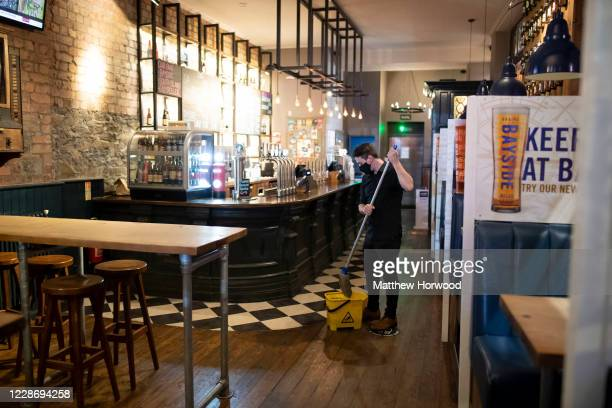 Worker mops the floor in the Cambrian Tap pub on September 24, 2020 in Cardiff, Wales. Pubs, cafes and restaurants in Wales will have to shut at...