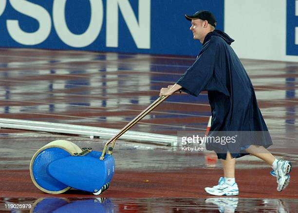 A worker mops water from the track during rain delay in the IAAF World Championships in Athletics at Olympic Stadium in Helsinki Finland on Tuesday...