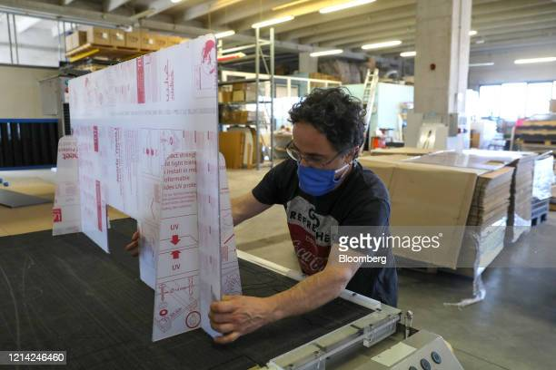 A worker mounts a plexiglass screen to test cuts at Plexismart Srl in Guidonia close to Rome Italy on Wednesday May 20 2020 Floortoceiling plexiglass...