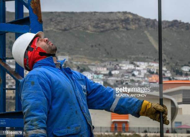 A worker mounts a pump jack at Bibi Heybat Oil Field situated at the coast of the Caspian Sea outside Baku on March 19 2019 Bibi Heybat's first oil...