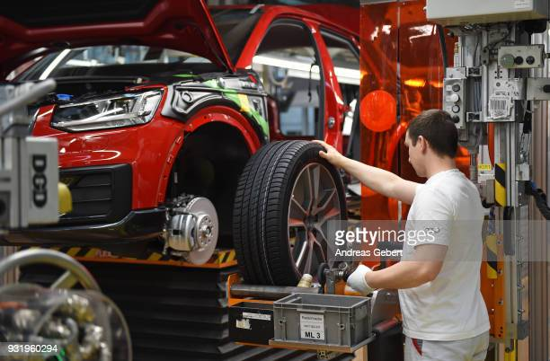 Worker mounts a wheel to an Audi sedan on an assembly line at the Audi automobile plant on March 14, 2018 in Ingolstadt, Germany. U.S. President...