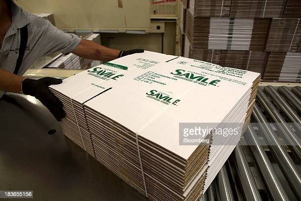 A worker moves a bundle of Savile shampoo boxes on the conveyor belt inside the BioPappel Kraft packaging plant in Tizayuca Hidalgo Mexico on...