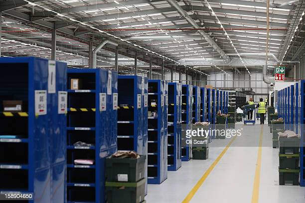 A worker moves a cart in the giant semiautomated distribution centre where the company's partners process the online orders for the John Lewis...