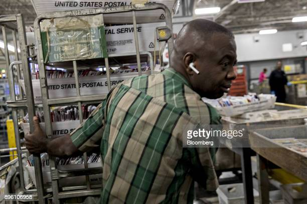 A worker moves a cart stacked with trays of mail at the United States Postal Service Suburban processing and distribution center in Gaithersburg...