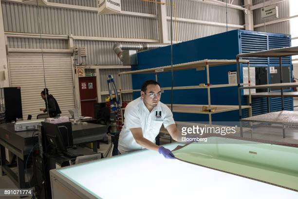A worker moves a component for the helicopter fuselage on a workstation at the Tighitco Inc manufacturing facility in San Luis Potosi Mexico on...