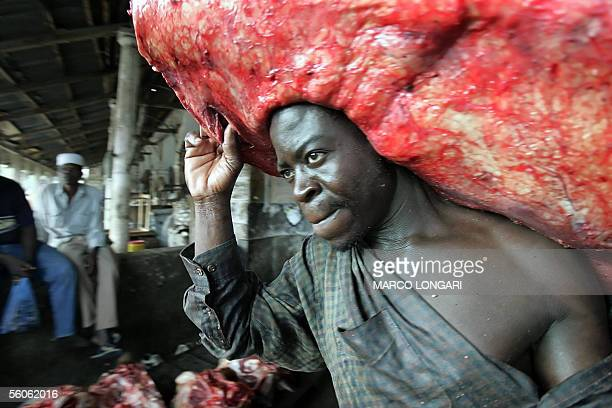 A worker moves a slab of meat 03 November 2005 across the reopened Darajani market in Stone Town Zanzibar The market as well as the largest part of...