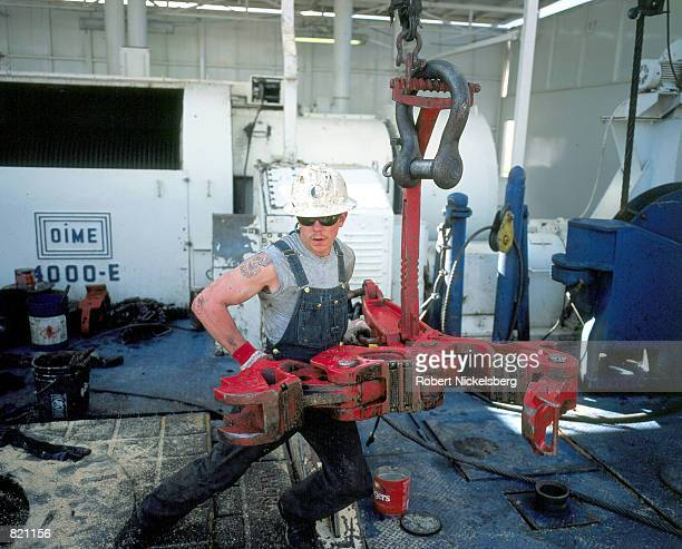 A worker moves a vice clamp to hold drilling pipe March 19 2001 on a natural gas drilling rig in Lysite Wyoming Workers are pulling up 8900 hundred...