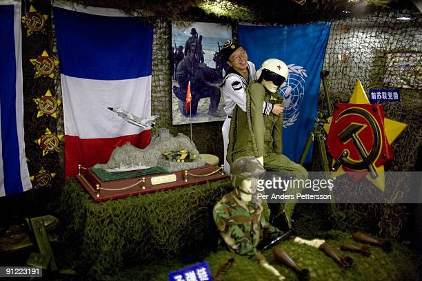 A worker moves a Western soldier mannequin at Minsk World Theme Park on October 1 2008 outside Shenzhen China The Minsk an aircraft carrier was built...
