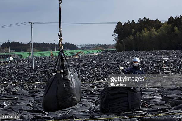 A worker moves bags of nuclear waste in an evacuation zone area damaged by the 2011 earthquake and tsunami in Tomioka Fukushima Prefecture Japan on...