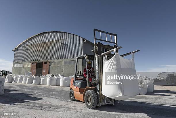 A worker moves bags of potassium chloride near the Potassium KCL Pilot facility inside the Salar de Uyuni in Potosi Bolivia on Saturday Dec 10 2016...