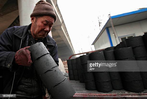 Worker moves coal briquettes onto a pedicabat at a coal distribution business in Huaibei, central China's Anhui province on January 30, 2013....