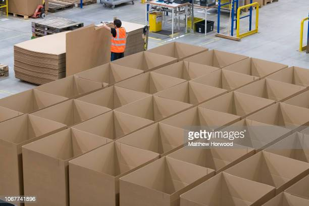 A worker moves large cardboard sheets in the Amazon fulfillment centre as workers gear up for Black Friday and Christmas on November 13 2018 in...