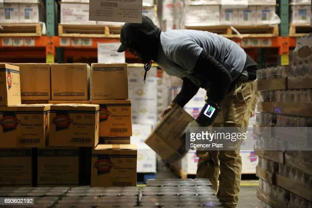 A worker moves pallets of food at the Food Bank for New York City's main warehouse in the Bronx neighborhood of Hunts Point on June 7 2017 in New...