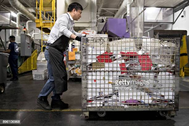 A worker moves piles of mail in a cart at the United States Postal Service Suburban processing and distribution center in Gaithersburg Maryland US on...