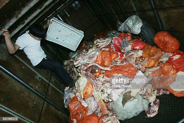 Worker moves spoiled pork to a truck under the direction of officers with the Beijing Health Supervision Institute at a freezer of the Huilongguan...