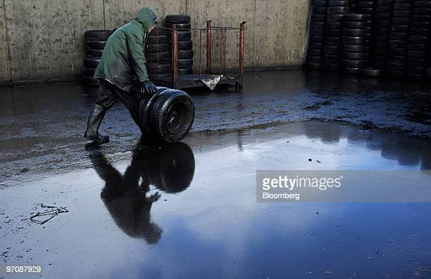 A worker moves tires salvaged from a damaged car at Allo Casse Auto's car demolition site in Athis Mons France on Wednesday Feb 24 2010 French...